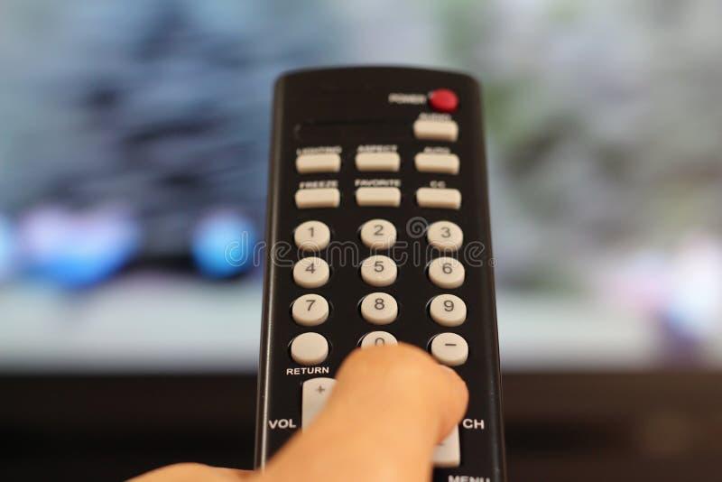Mão que guarda um controlador do telecontrole da tevê imagem de stock