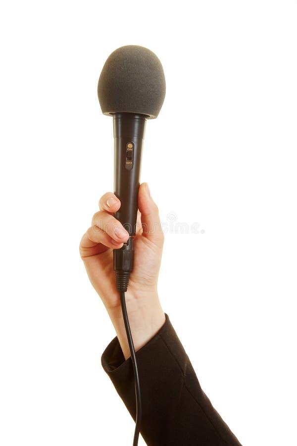 Mão que guarda um microfone foto de stock