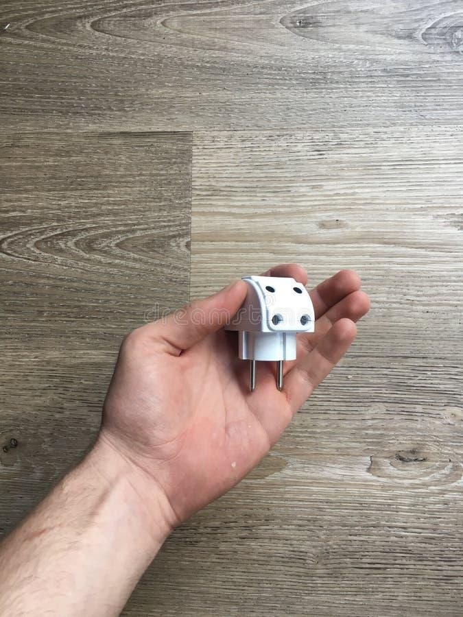 Mão que guarda um multiplug branco fotografia de stock royalty free