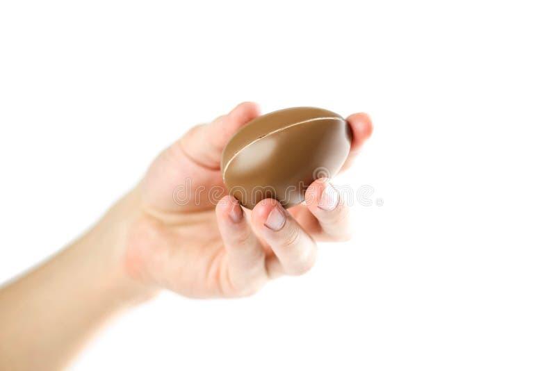 Mão que guarda um ovo de chocolate Fim acima Isolado no fundo branco fotos de stock royalty free