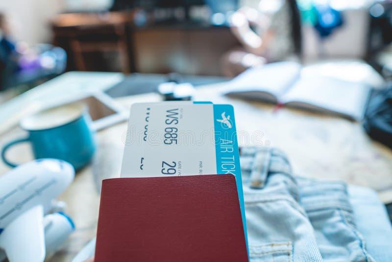 Mão que guarda um passaporte e dois bilhetes no fundo da câmera, o mapa do mundo Prepara??o para a viagem fotografia de stock