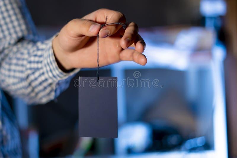 Mão que guarda um preço vazio com espaço f da cópia foto de stock