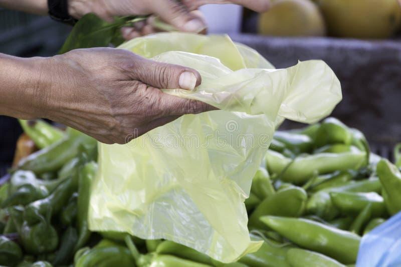 Mão que guarda um saco de plástico amarelo no mantimento imagem de stock
