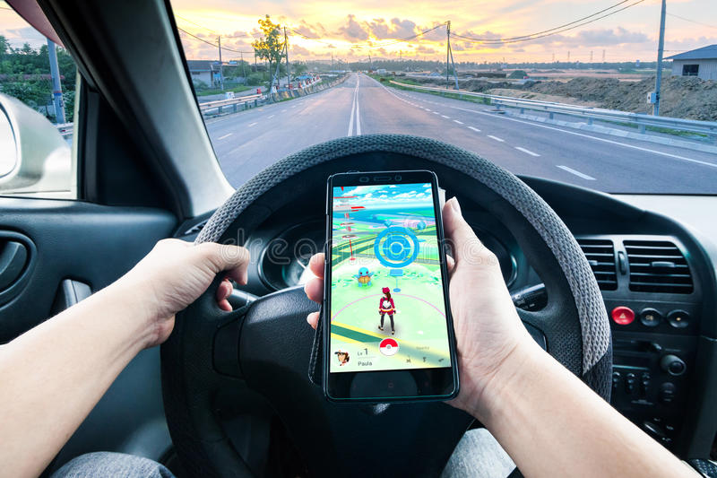 A mão que guarda um telefone celular que joga Pokemon vai jogo ao conduzir fotos de stock