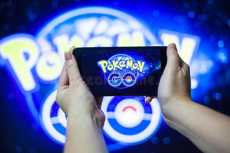 A mão que guarda um telefone celular que joga Pokemon vai jogo com fundo do borrão fotografia de stock royalty free
