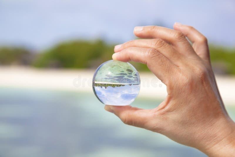 Mão que guardara uma bola de vidro pequena imagens de stock