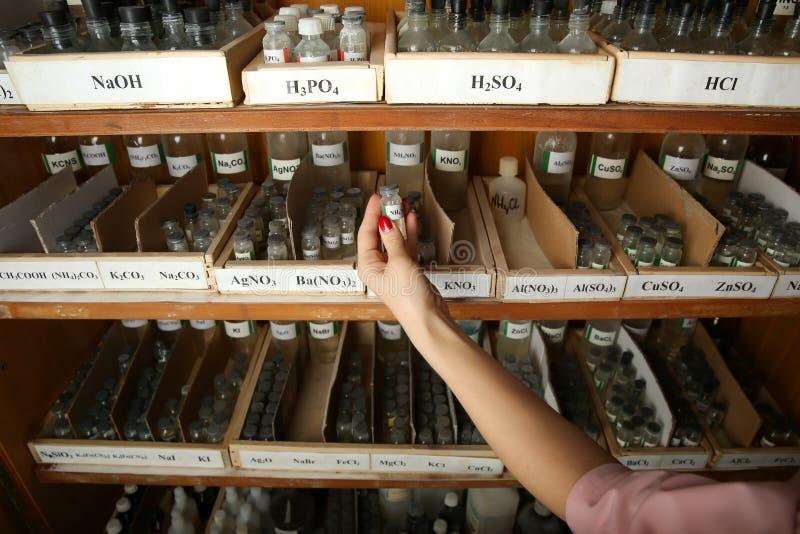 M?o que guarda uma garrafa com reagente qu?mico fotos de stock