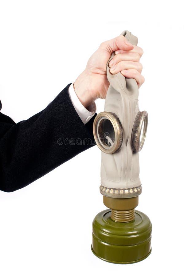Mão que guarda uma máscara de gás imagem de stock