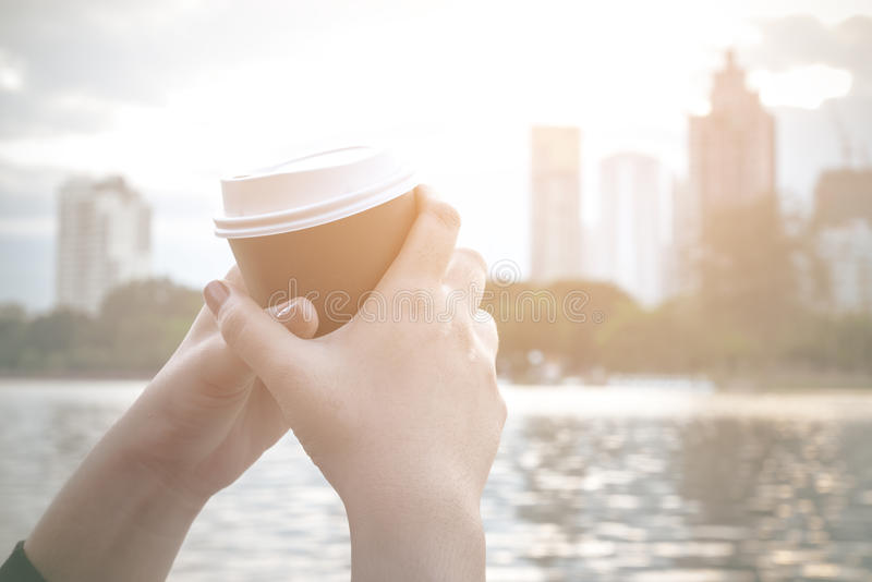 Mão que guarda a xícara de café na arquitetura da cidade foto de stock