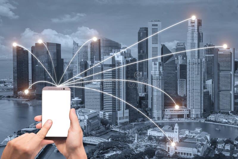 A mão que guardam o telefone esperto e a cidade de Singapura com rede conectam fotografia de stock