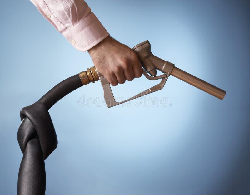 Mão que guardara a bomba de combustível com nó na tubulação fotografia de stock royalty free