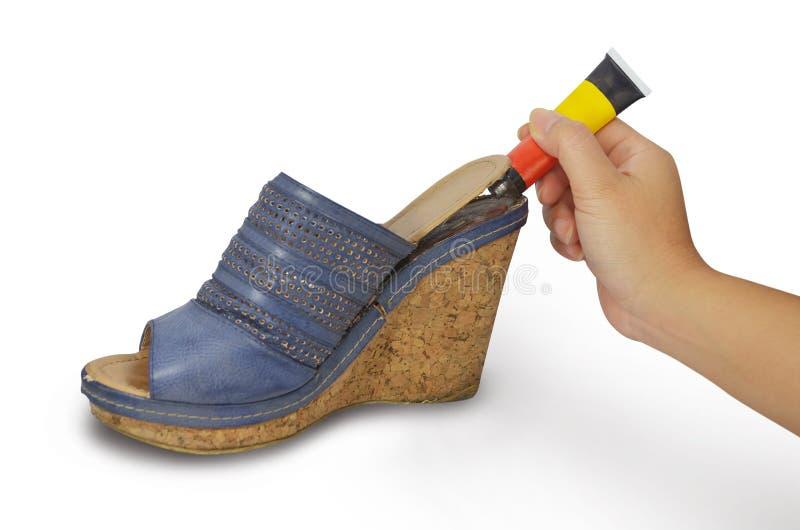 Mão que guardara a colagem que repara a sapata fotografia de stock