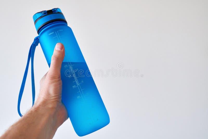 Mão que guardara a garrafa de água fotografia de stock