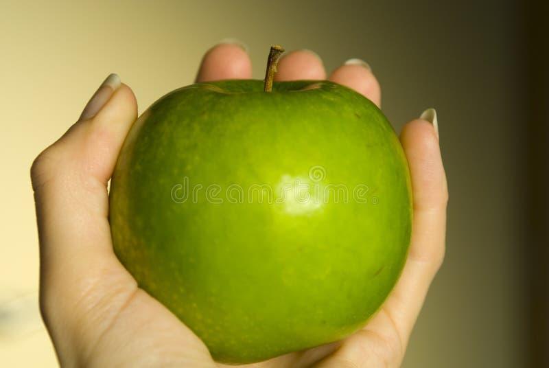 Mão que guardara a maçã fotografia de stock