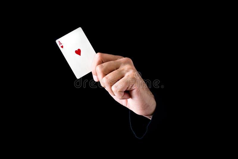 Mão que guardara o ás do cartão dos corações foto de stock