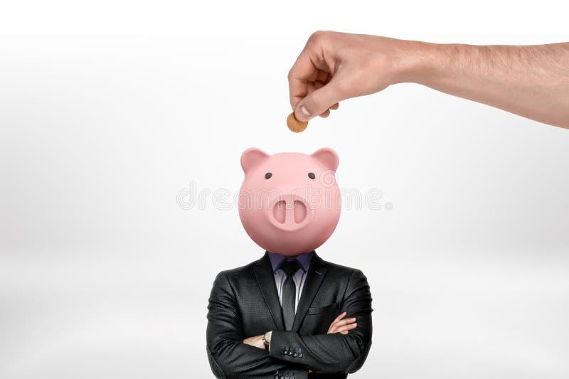 Mão que introduz a moeda na cabeça do mealheiro de um homem de negócios no fundo branco foto de stock