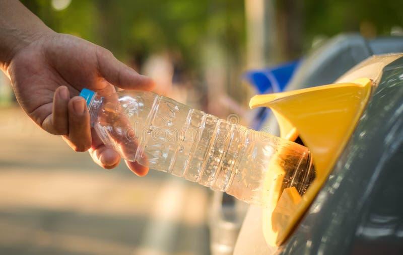 Mão que joga a garrafa plástica no escaninho de reciclagem, aquecimento global fotografia de stock royalty free