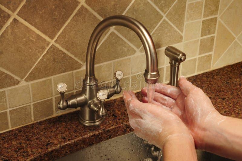Mão que lava sob a água que flui para fora um faucet fotografia de stock