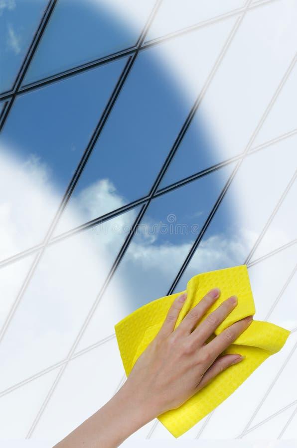 Mão que limpa uma superfície de vidro de uma construção imagens de stock royalty free