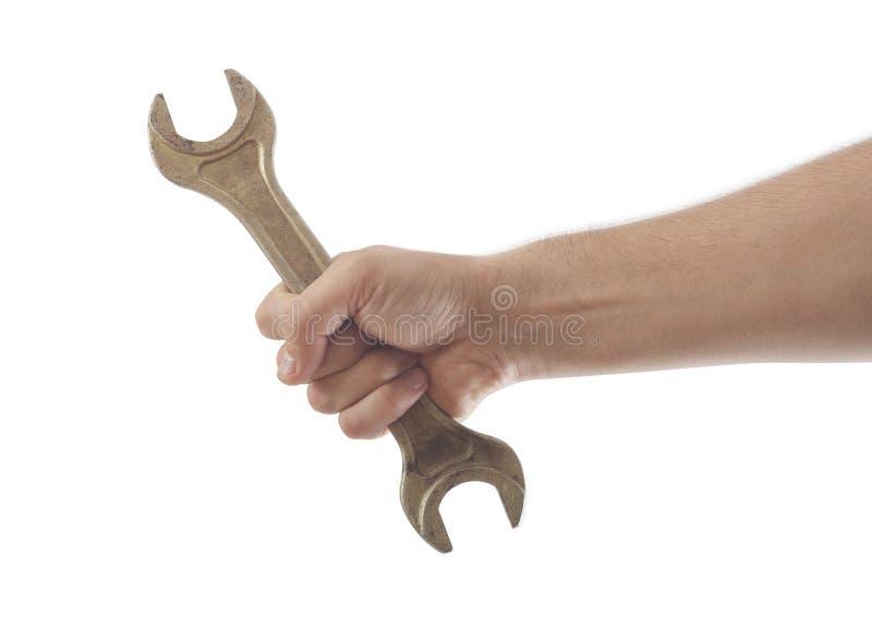 Mão que mantém a ferramenta da chave isolada imagens de stock royalty free