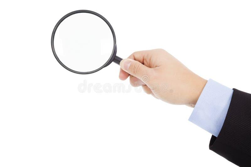 Mão que mantém a lente de aumento de vidro fotografia de stock