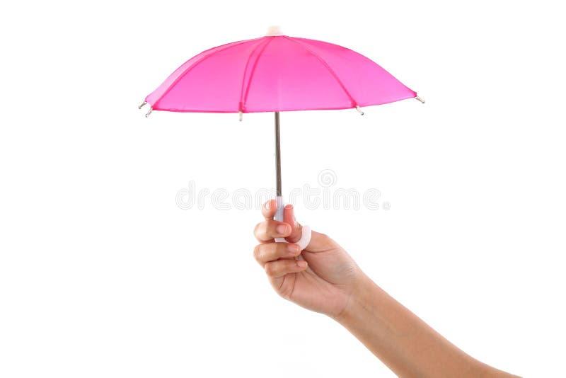 Mão que mantém o guarda-chuva pequeno contra o branco fotos de stock