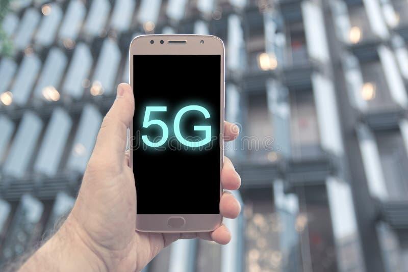 Mão que mantém um smartphone 5G móvel compatível contra uma fachada de construção moderna em Barelona foto de stock royalty free