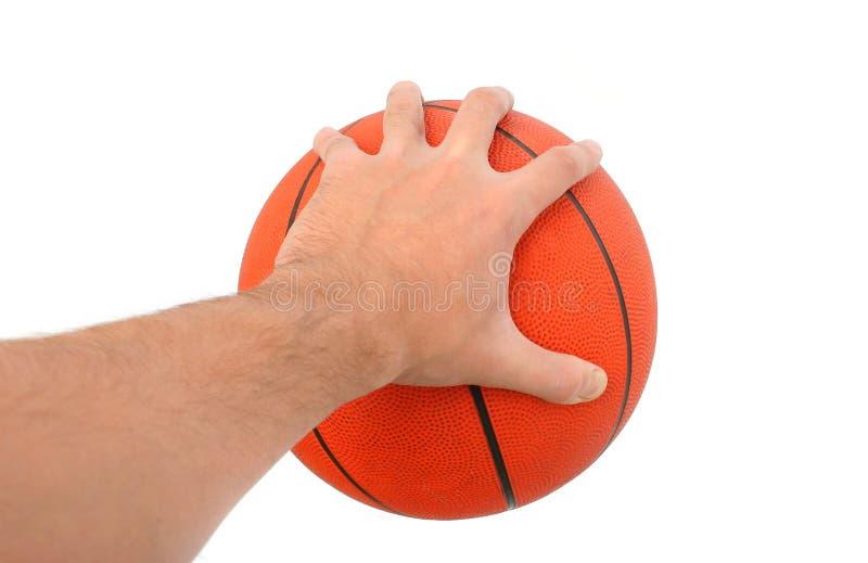 Mão que mantem uma esfera do basquetebol isolada fotografia de stock royalty free