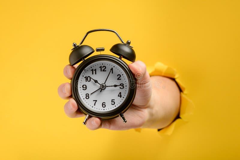 Mão que mostra um despertador imagens de stock