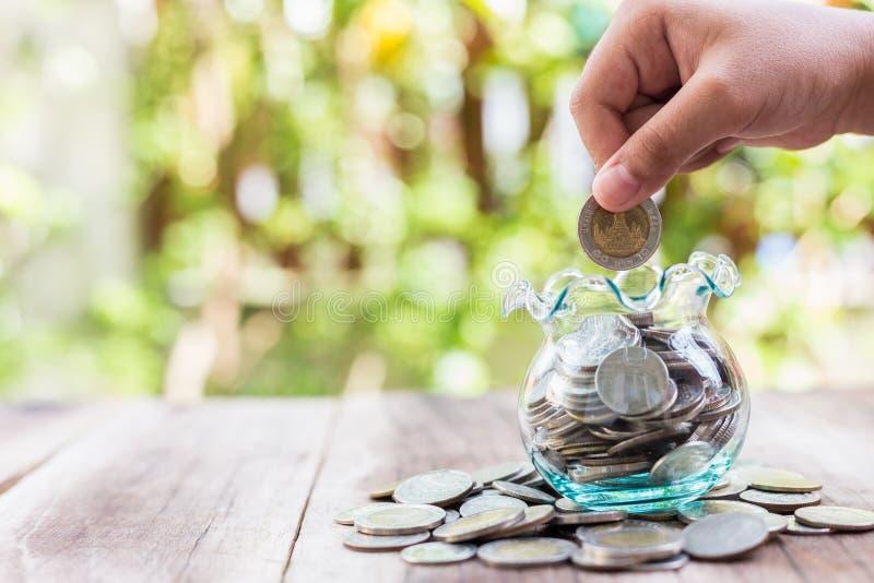 Mão que põe moedas no frasco do dinheiro Conceito das economias fotografia de stock
