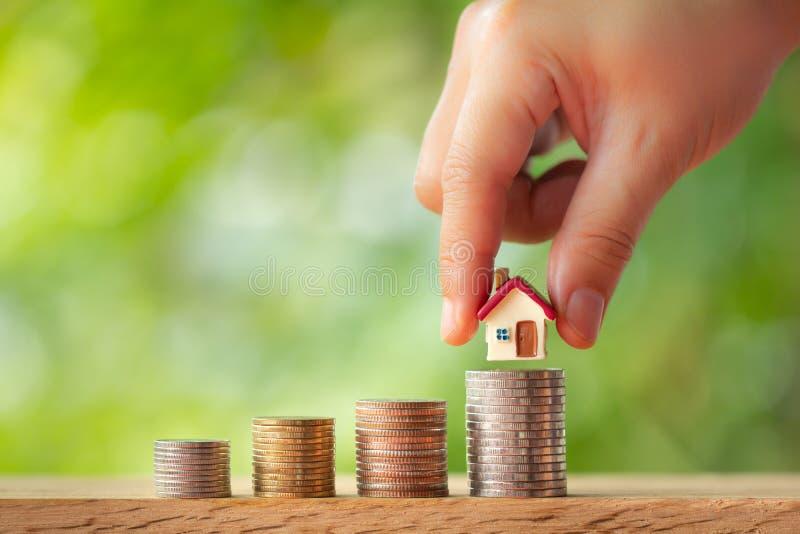 Mão que põe o modelo da casa sobre pilhas da moeda foto de stock royalty free