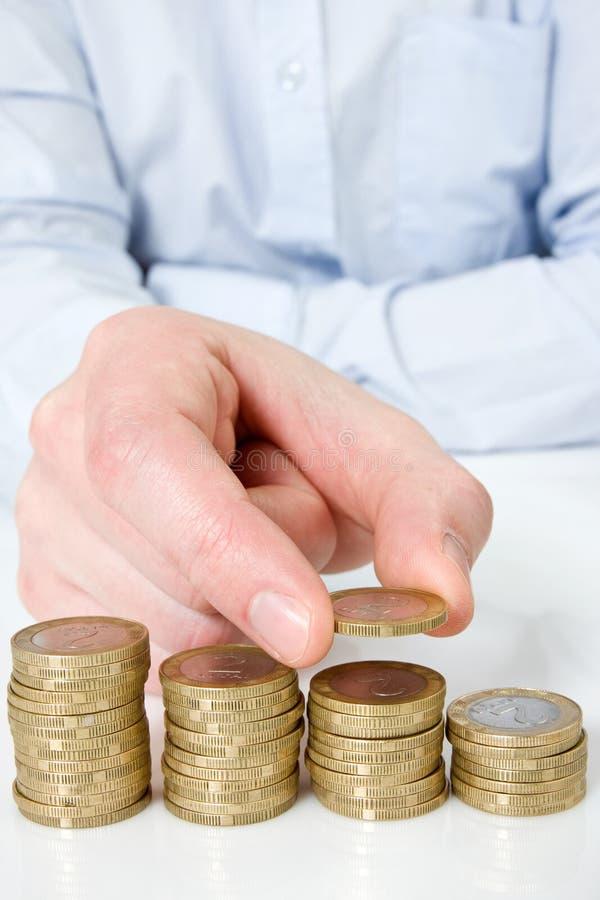 Mão que põr a moeda à escadaria do dinheiro imagem de stock
