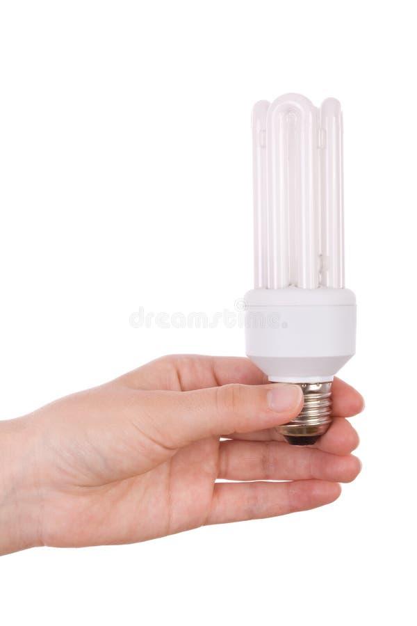 Mão que prende a ampola fluorescente compacta foto de stock royalty free