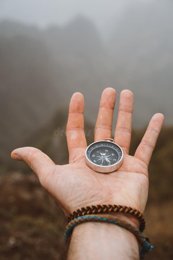 Mão que prende um compasso Silhueta da formação monumental da montanha no fundo fotos de stock