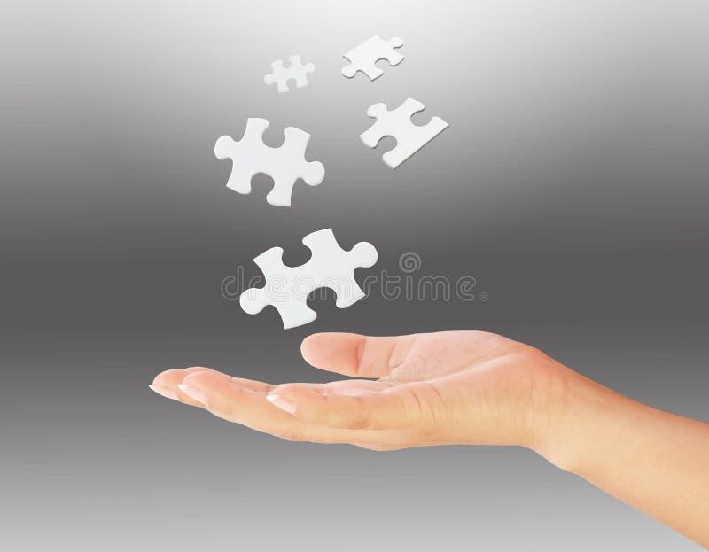 A mão que prende um enigma remenda. imagens de stock