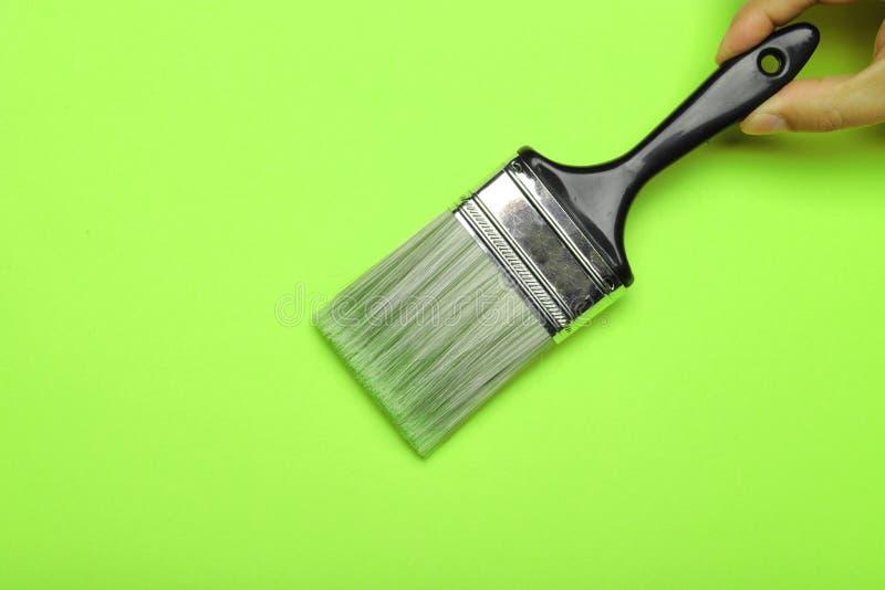 Mão que prende uma escova de pintura imagem de stock