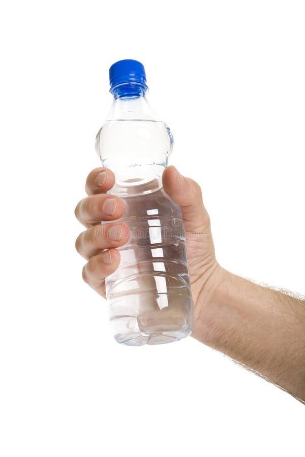 Mão que prende uma garrafa de água foto de stock royalty free