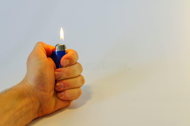 Mão que queima um isqueiro no fundo branco imagens de stock