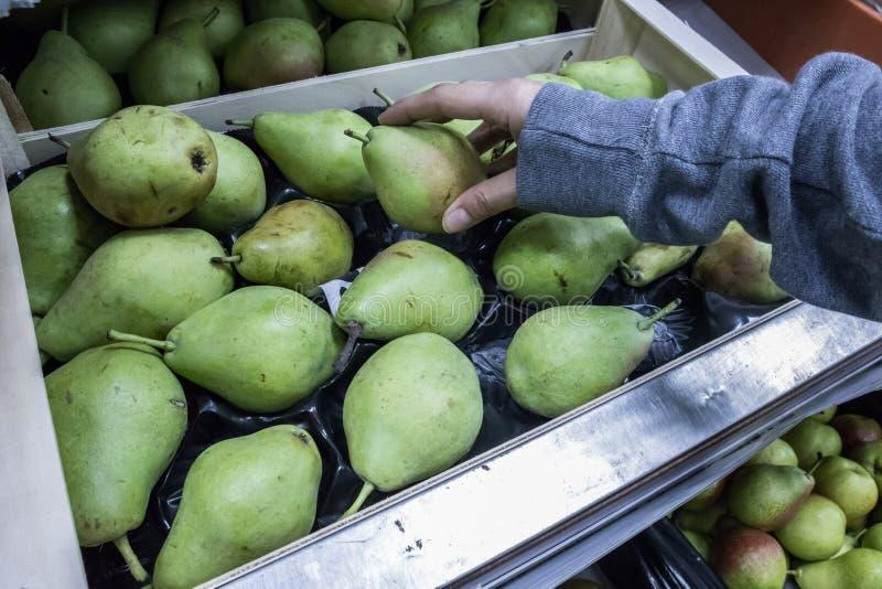 M?o que repica a pera no supermercado fotografia de stock