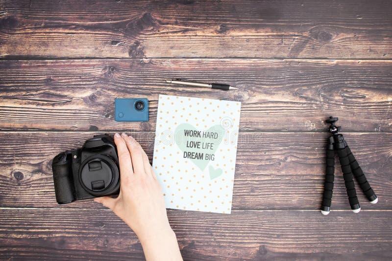 Mão que toma fontes da câmera e da fotografia na tabela imagens de stock
