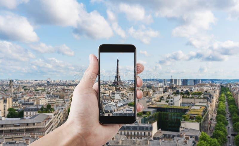 Mão que toma a foto da torre Eiffel, do marco famoso e do destino do curso em Paris, França pelo telefone esperto móvel fotografia de stock royalty free