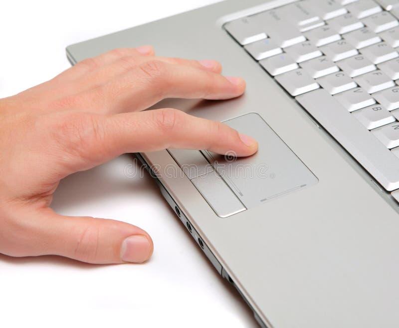 Mão que trabalha em um touchpad do portátil fotografia de stock