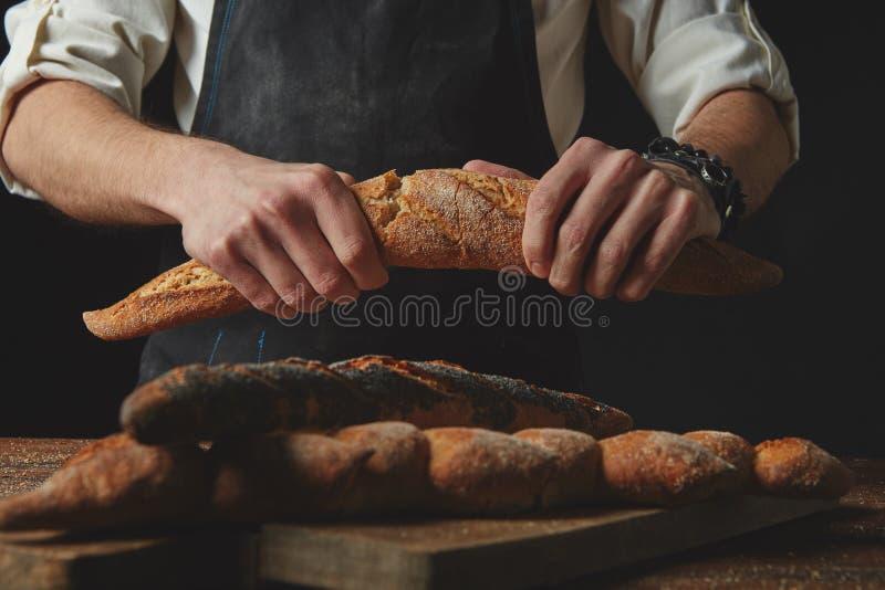 A mão quebra o baguette imagens de stock royalty free