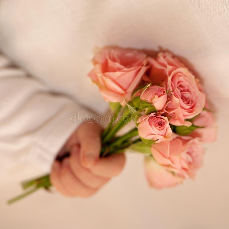 Mão recém-nascida do bebê que guarda rosas cor-de-rosa. imagem de stock royalty free