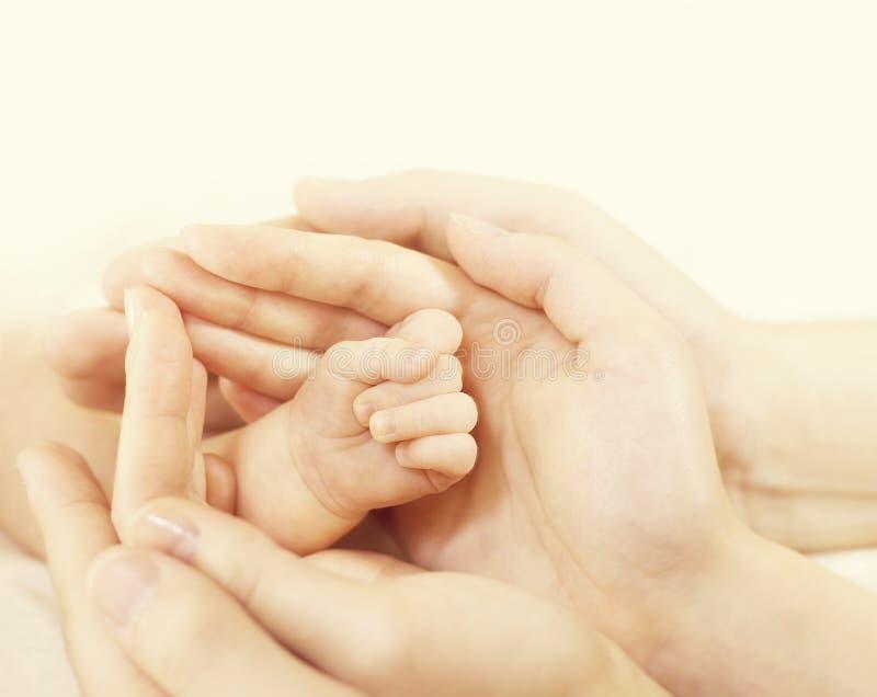 A mão recém-nascida nas mãos da família, posse do bebê dos pais protege recém-nascido imagem de stock royalty free