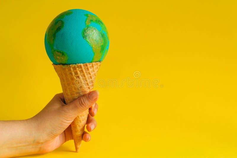 Mão segura cone de waffffle com modelo da Terra fotos de stock
