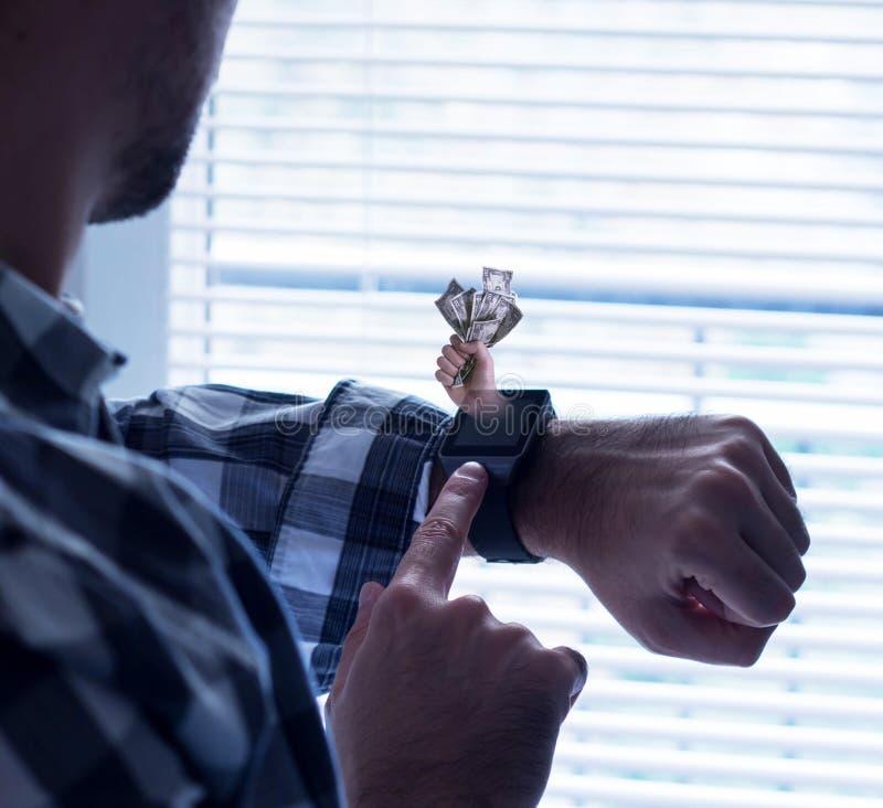 Mão segurando dinheiro saindo da tela do relógio inteligente fotos de stock royalty free