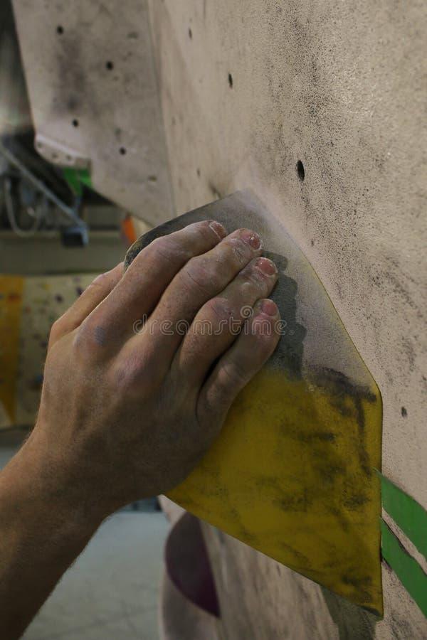 Mão suja do magnésio que guarda um aperto amarelo em uma parede bouldering fotos de stock