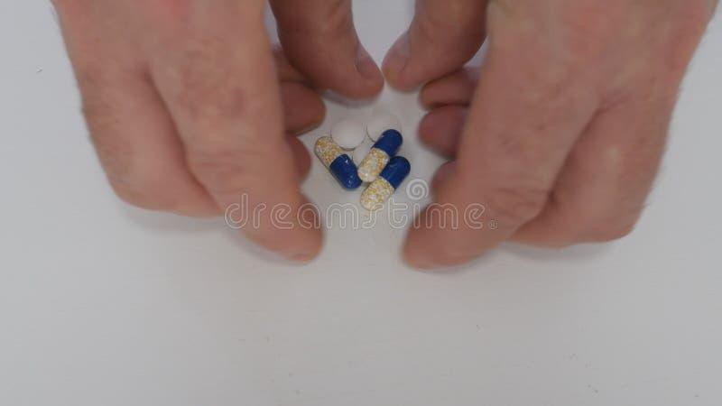 A mão superior que toma da tabela coloriu comprimidos médicos para a doença cardíaca imagens de stock royalty free