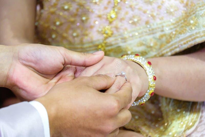 Mão tailandesa do ` s do noivo que põe uma aliança de casamento sobre o dedo do ` s da noiva imagens de stock